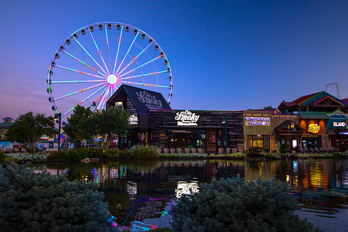 Pigeon Forge, Tennessee, USA - August 16, 2020: Lights reflected in a fountain with shops in the foreground and the Great Smoky Mountain Skywheel in the background at the Island in downtown Pigeon Forge.