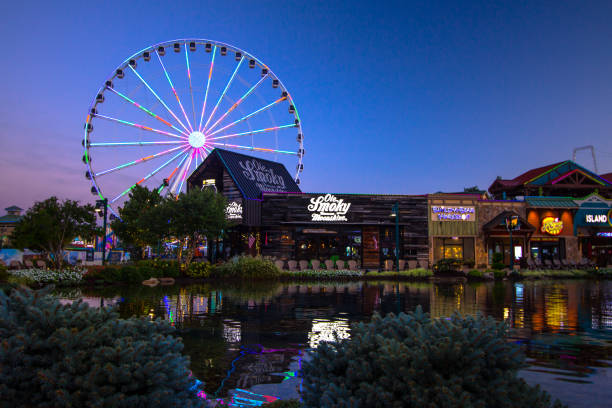Pigeon Forge Tennessee Cityscape Pigeon Forge, Tennessee, USA - August 16, 2020: Lights reflected in a fountain with shops in the foreground and the Great Smoky Mountain Skywheel in the background at the Island in downtown Pigeon Forge. pigeon forge stock pictures, royalty-free photos & images