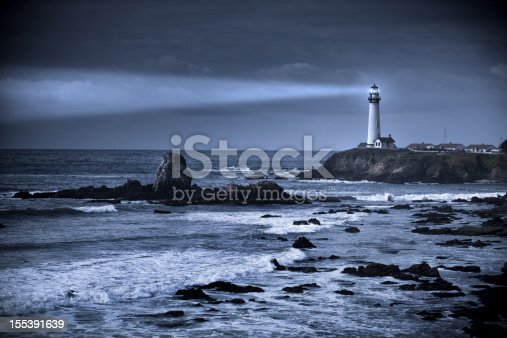 Pacific ocean waves crash the rocky beach coast by the Pigeon Point lighthouse in California by the Cabrillo highway US 1.  It is California's most-photographed light house and the tallest one on the Pacific Coast
