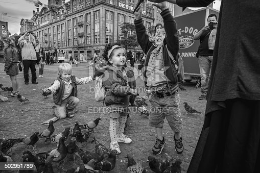 Amsterdam, Holland- June 17, 2014. Dam Square, near Royal Palace of Amsterdam and National Monument across. People enjoying feeding pigeons on the square.
