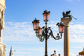 Pigeons are sitting on a lamppost in St. Mark Square in Venice, Italy