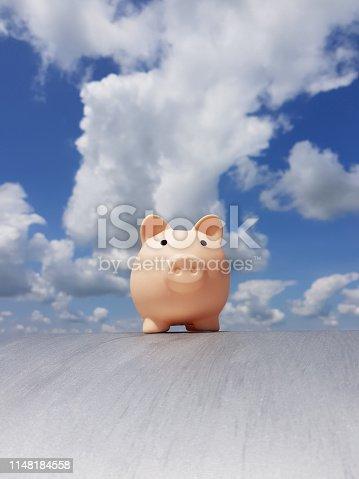 Piggy Bank against beautiful blue cloudy sky