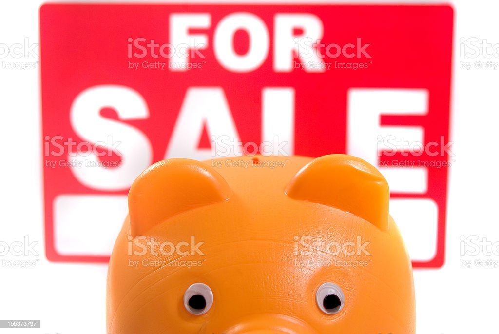 piggy bank and for sale sign isolated on white royalty-free stock photo