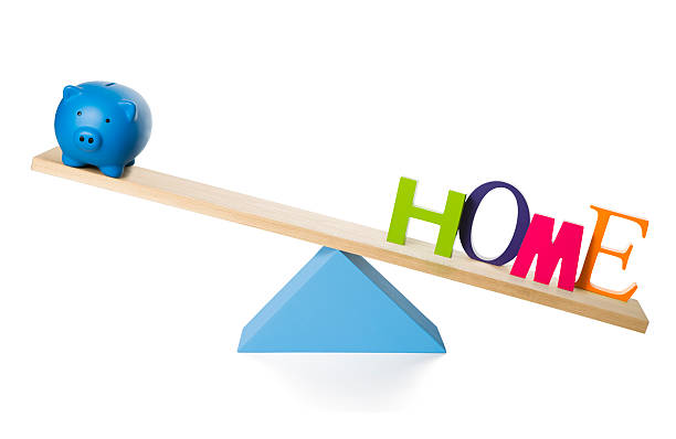Piggy bank and HOME on SeeSaw stock photo