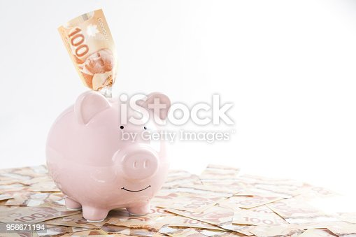Piggy bank and large amount of canadian one hundred dollar bills, saving/financial concept.