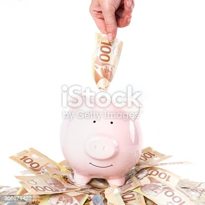 Hand inserting money into piggy bank and large amount of canadian one hundred dollar bills, saving/financial concept.