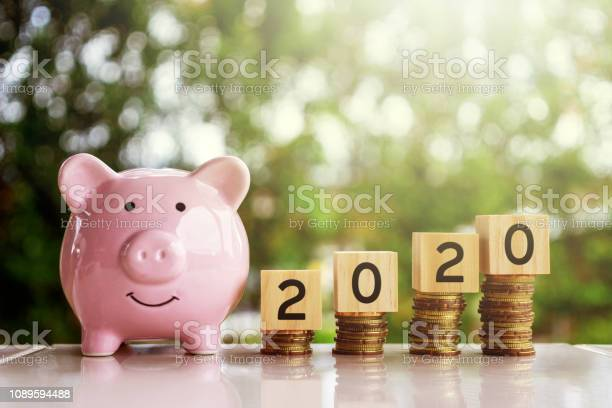 Piggy bank and wooden block with number 2020 on top of coins stack