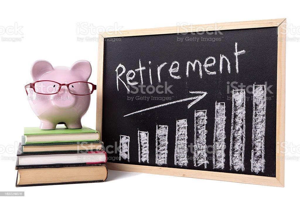 Piggy bank atop books by retirement savings chart royalty-free stock photo