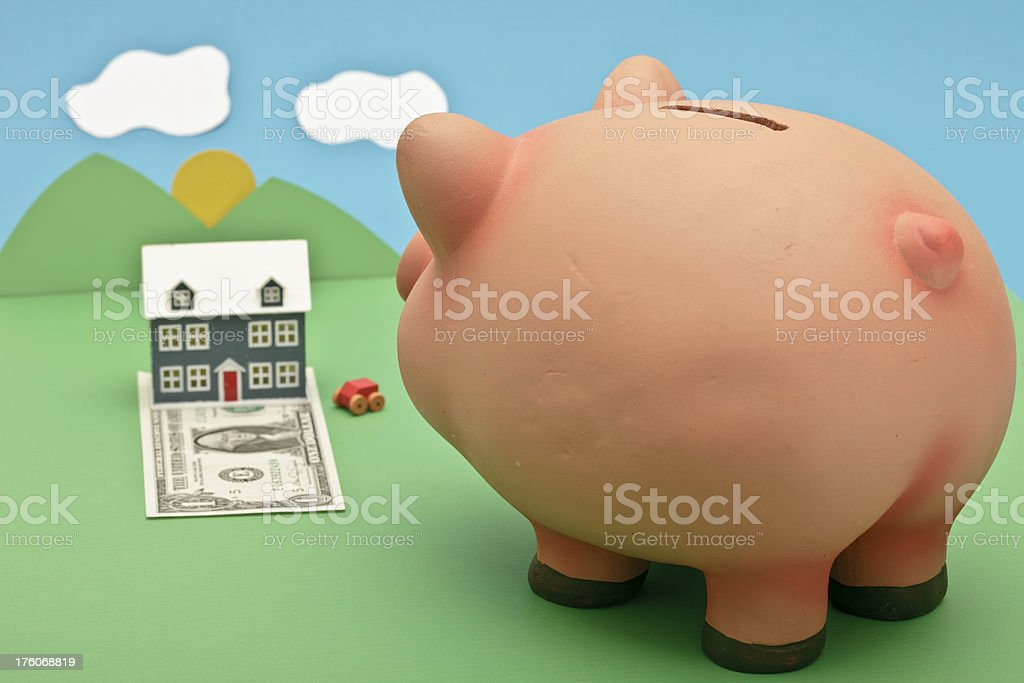 Piggy bank daydreaming with a house royalty-free stock photo