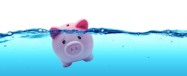 piggy bank drowning in debt - savings to risk - bankruptcy stock pictures, royalty-free photos & images
