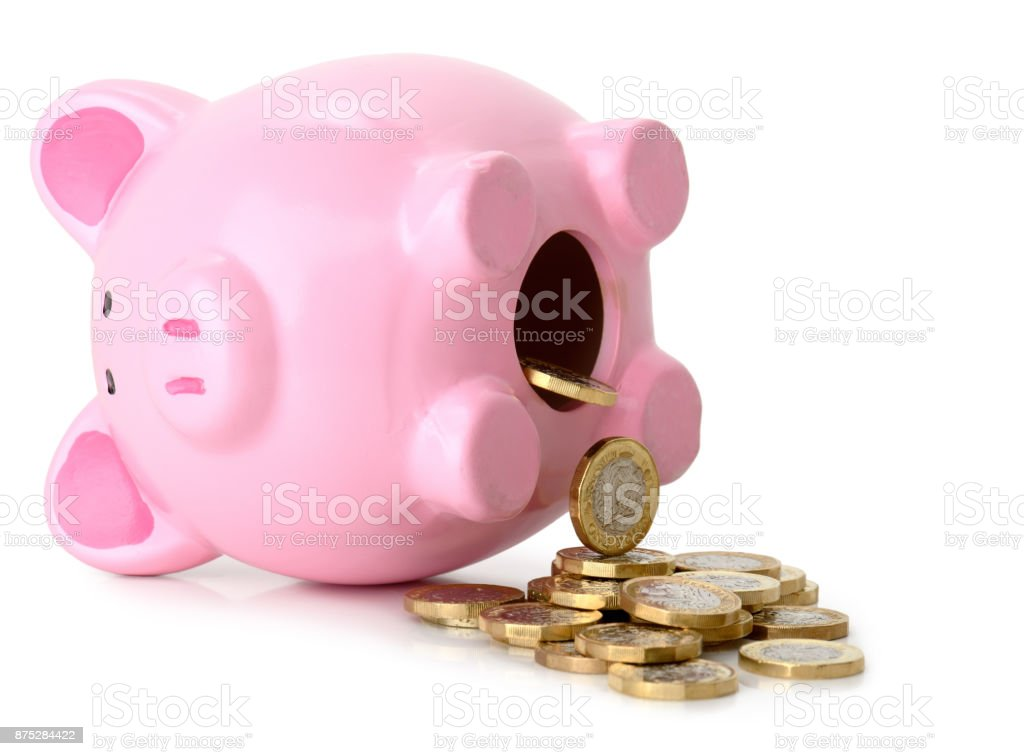 Piggy bank fallen on its side with coins pouring stock photo