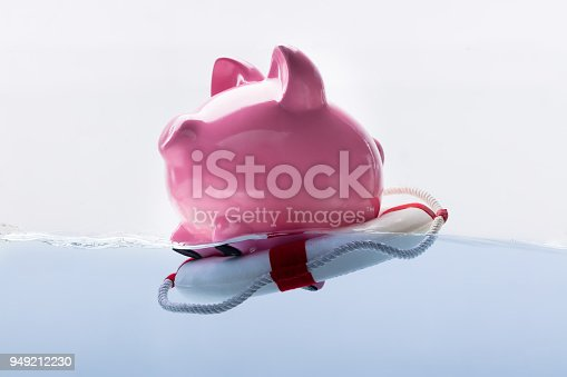 istock Piggy Bank Floating On Lifebuoy 949212230