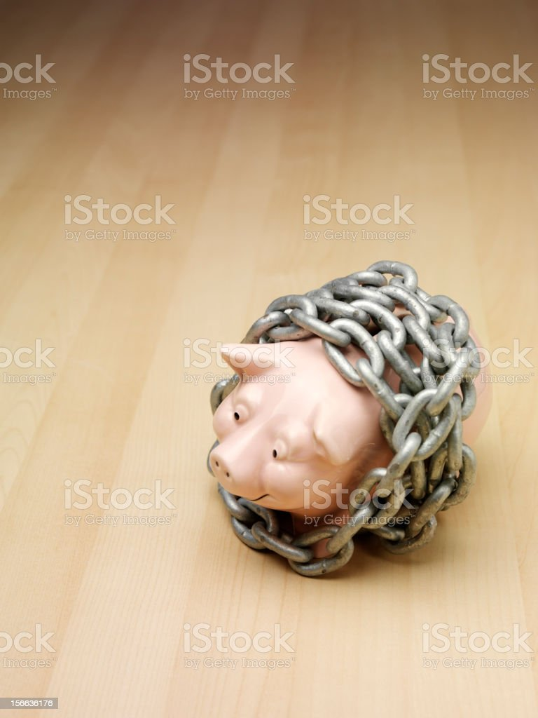 Piggy Bank in Chains on the  Floor royalty-free stock photo