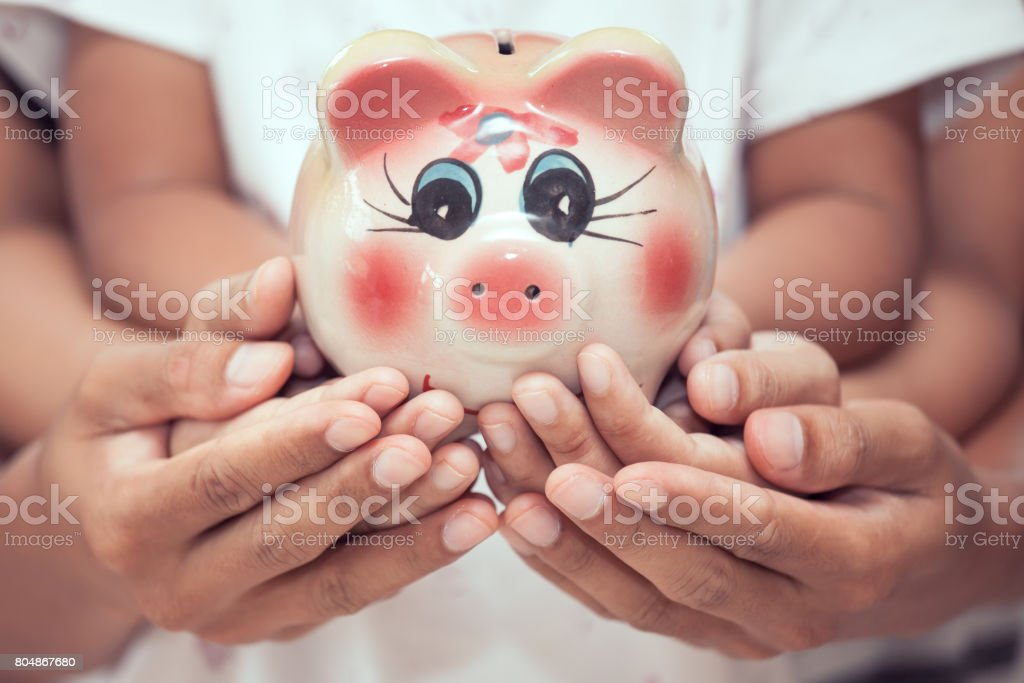 Piggy bank in child kid ,mother and father hands in vintage color tone stock photo