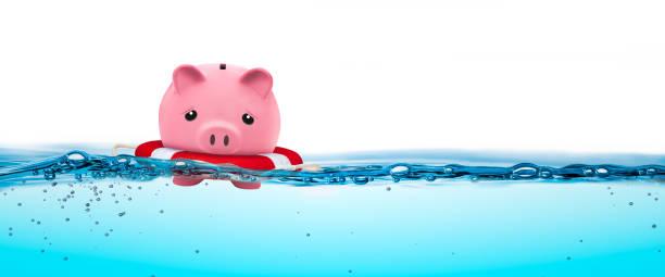 piggy bank in life-ring - wasser sicherheitsausrüstung stock-fotos und bilder
