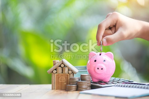 istock Piggy bank is placed on the calculator. house and coin placed on the side. planning savings money of coins to buy a home concept for property, 1206880088