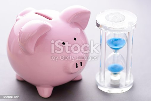 istock Piggy bank near classic hourglass with blue sand 638981132
