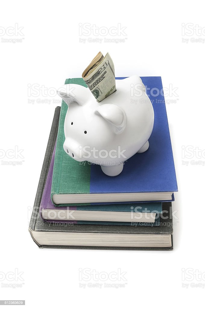 Piggy bank on a stack of books stock photo