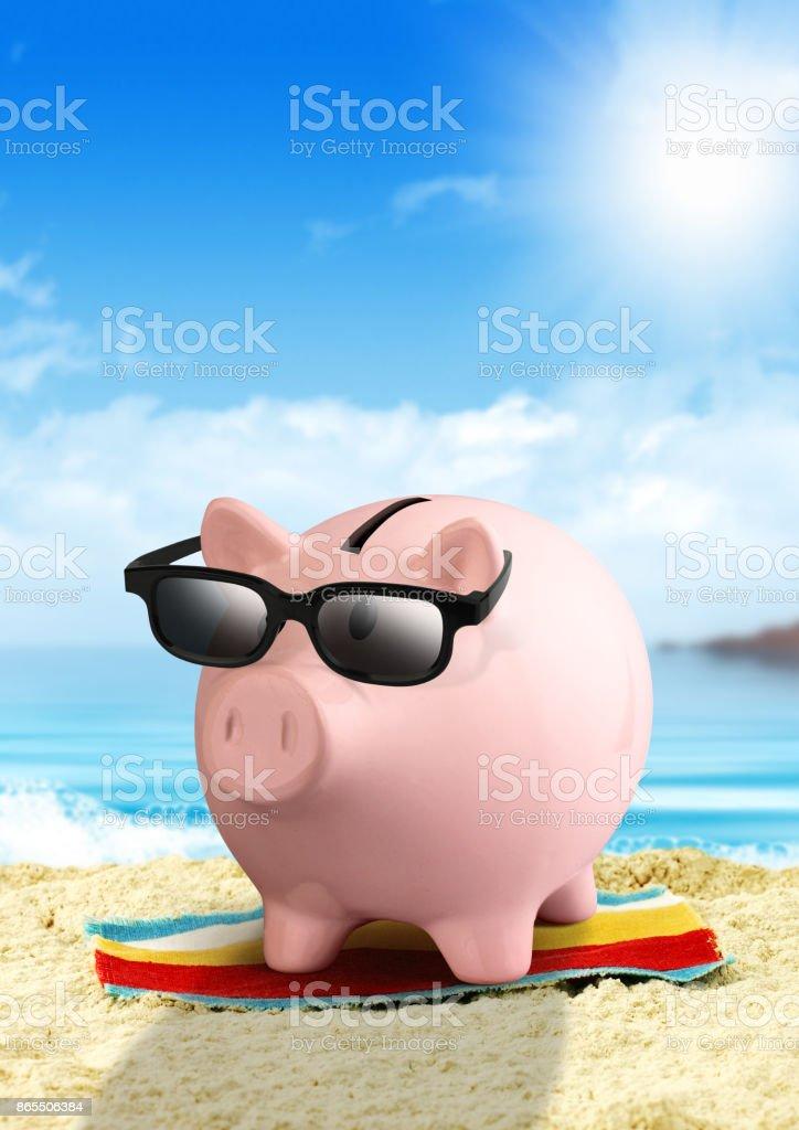 Piggy bank on beach, money for travel concept stock photo