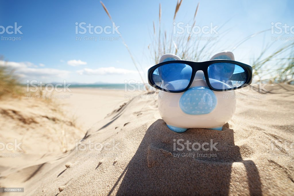 Piggy Bank on beach vacation stock photo