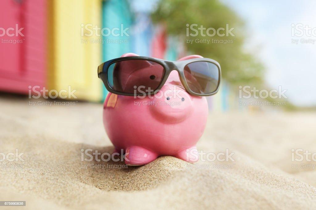 Piggy bank on beach vacation stock photo
