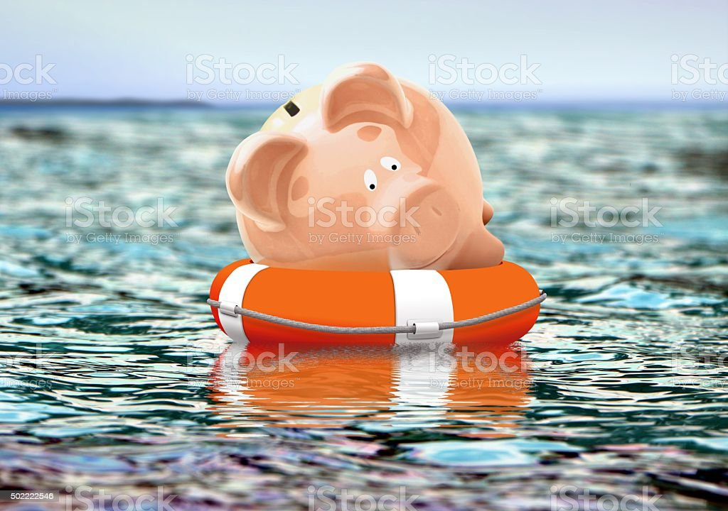 Piggy bank on buoy floating on water stock photo