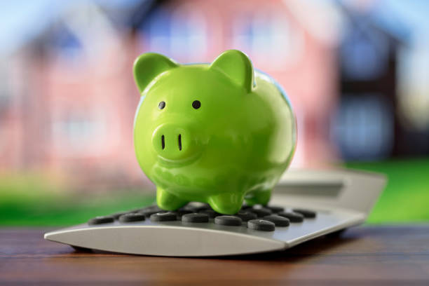 Piggy bank on calculator in front of property, saving to buy a house, real estate or home savings stock photo