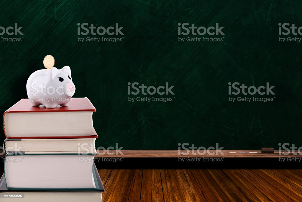Piggy Bank on Stack of Books and Chalkboard Background stock photo