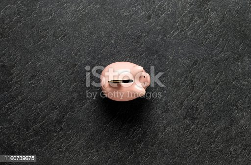 Piggy bank, penny bank, money box pink ceramic/porcelain with coin from above on dark stone background