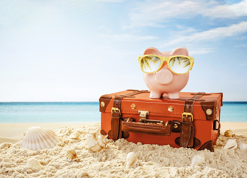 istock Piggy bank resting on the tropical beach 1153000917