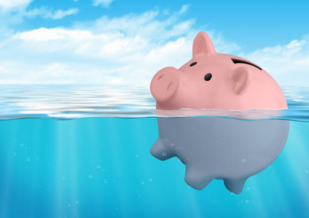 Piggy bank sinking, savings loss concept stock photo