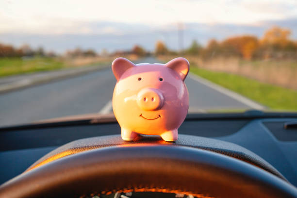 Piggy Bank sitting on the dashboard during driving a car stock photo