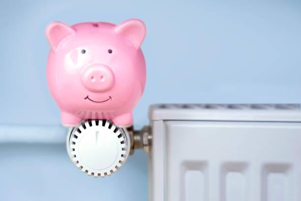 Piggy bank sitting on the heater stock photo