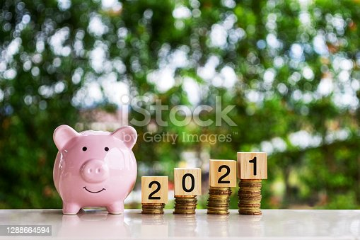 Piggy Bank and 2021 number on wood block on top of stack of coins