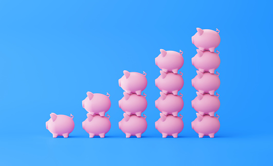 Piggy bank stacks forming a bar graph on blue background. Horizontal composition with copy space. Great use for savings concepts.