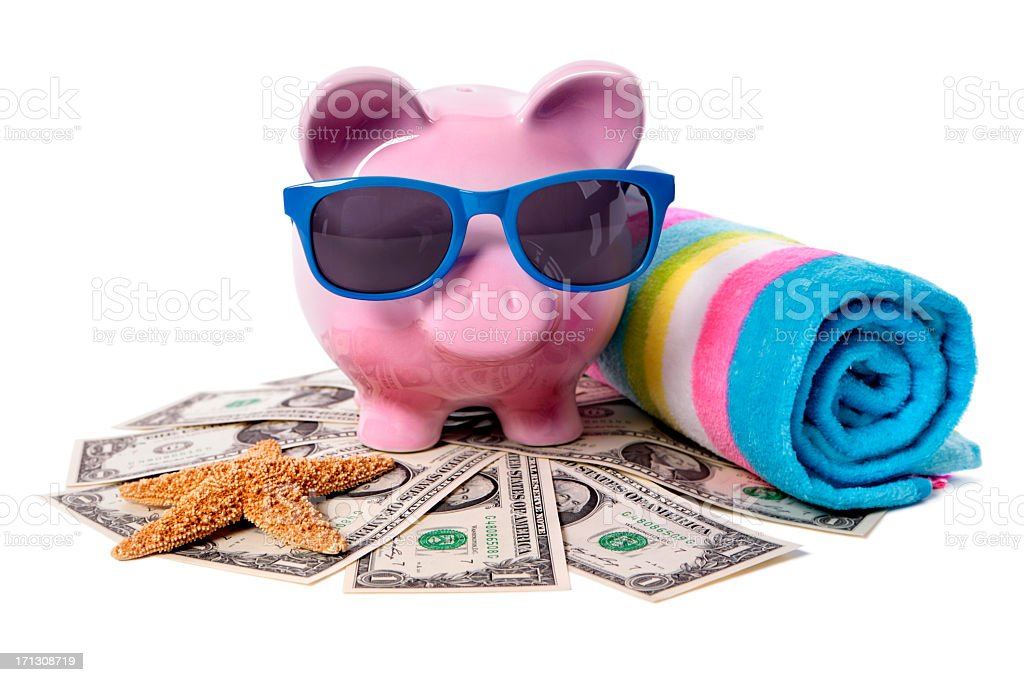 A piggy bank surrounded by money and beach items stock photo