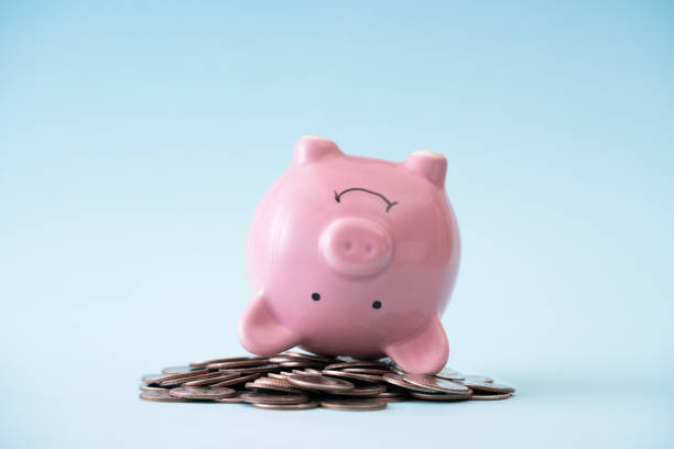 Piggy bank upside down on coin stack stock photo