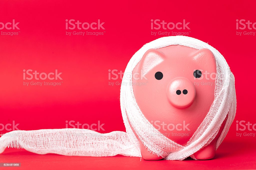 piggy bank with a white bandage stock photo