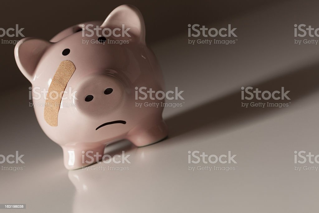 Piggy Bank with Bandage on Face stock photo