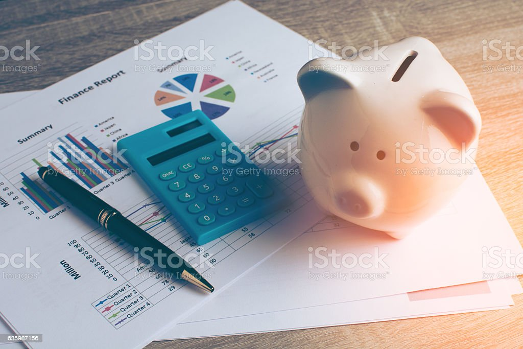 Piggy bank with business stuff. Piggy bank with business stuff, business and finance concept, vintage color tone. Accidents and Disasters Stock Photo