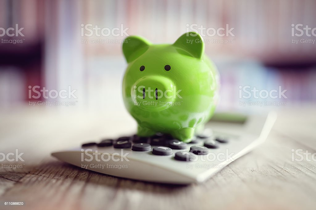 Piggy bank with calculator Piggy bank on calculator concept for saving, accounting, banking and business account Accountancy Stock Photo