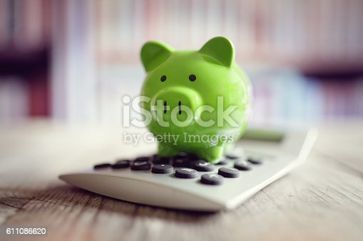 istock Piggy bank with calculator 611086620