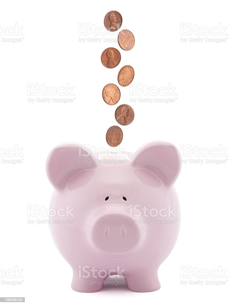Piggy bank with coins falling into slot stock photo