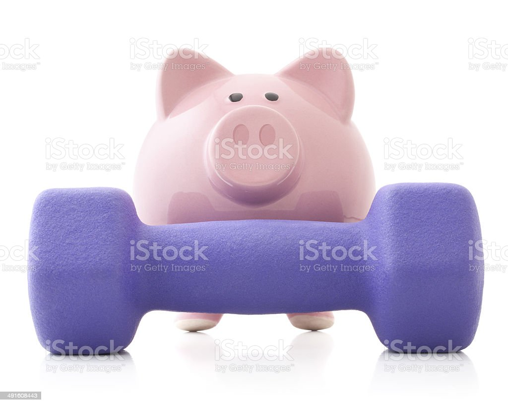 Piggy bank with dumbbell weights stock photo