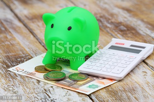Piggy bank with EUR banknotes and coins with calculator on rustic wooden surface