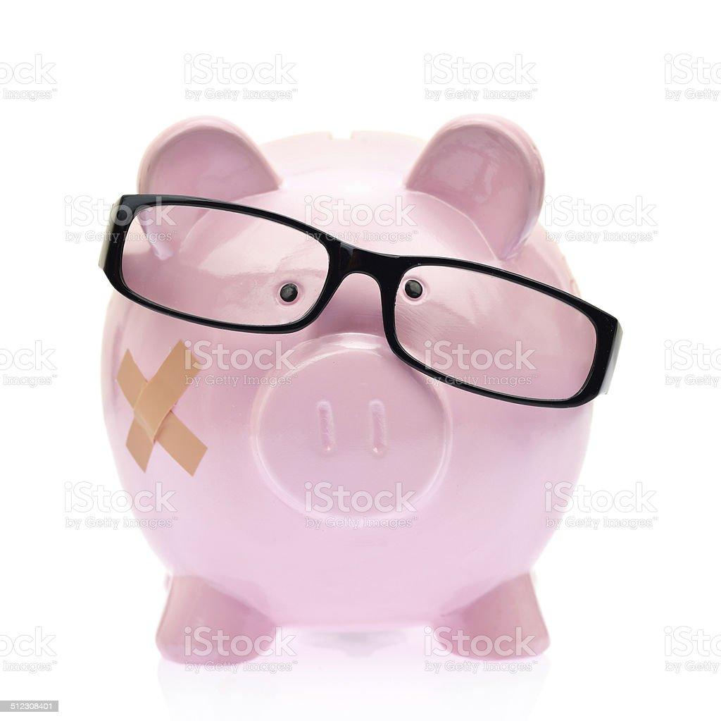 Piggy bank with eyeglasses and bandage stock photo