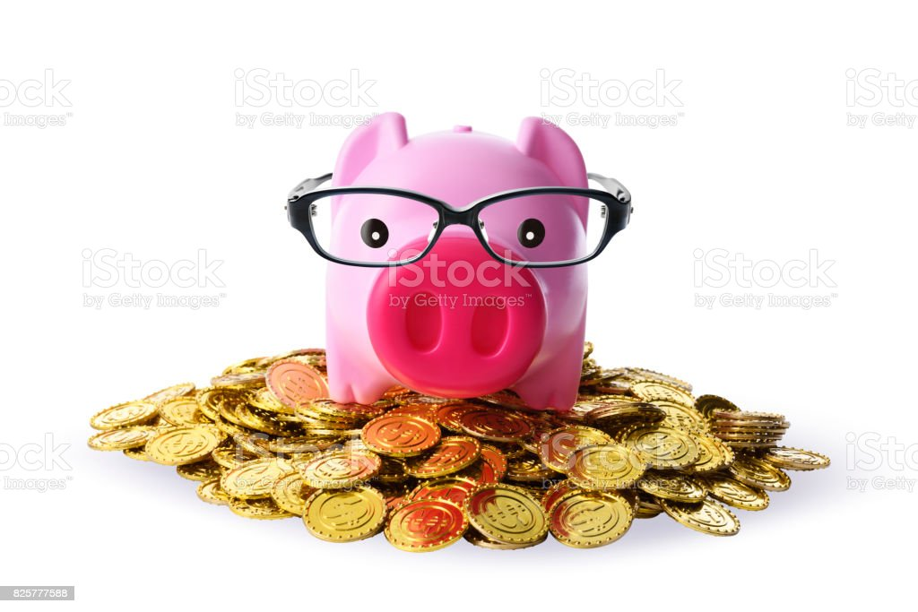 Piggy bank with eyeglasses on pile of golden coins on white background stock photo