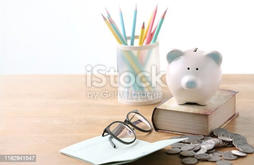 istock Piggy bank with glasses and black bank book, economical and educational concepts 1162941547