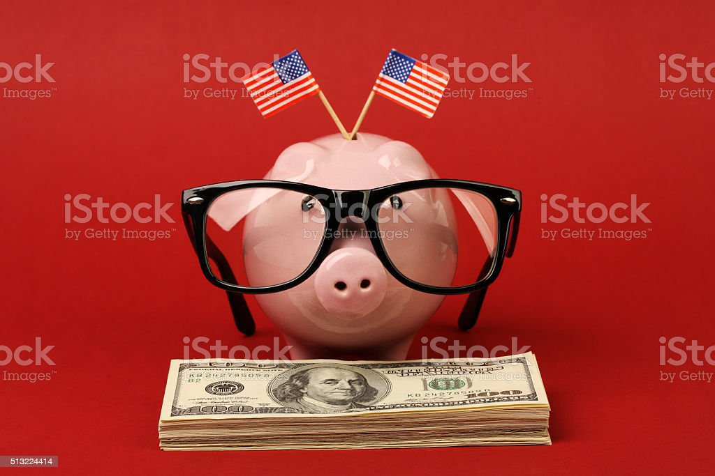 Piggy bank with glasses and two small USA flags stock photo