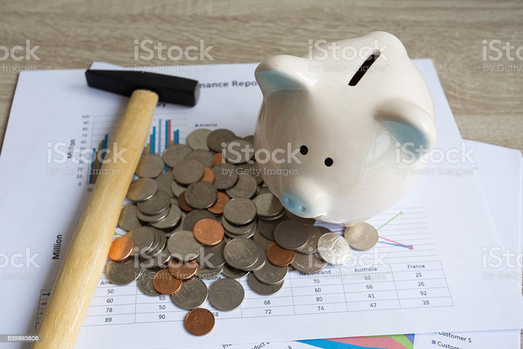 Piggy bank with hammer on wood table. stock photo